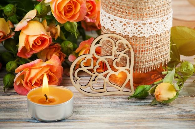 Flores frescas de rosas naranjas, corazón, botella de decoración y velas encendidas