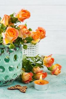 Flores frescas de rosas naranjas en un jarrón de menta y velas encendidas