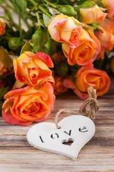 Flores frescas de rosas naranjas sobre superficie de madera