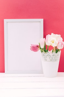 Flores frescas de tulipán en florero con marco de fotos en blanco