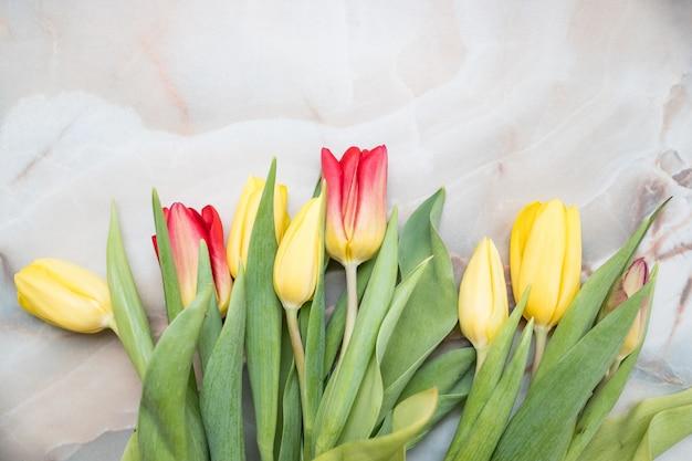 Flores frescas de tulipán rosa en mesa de piedra.