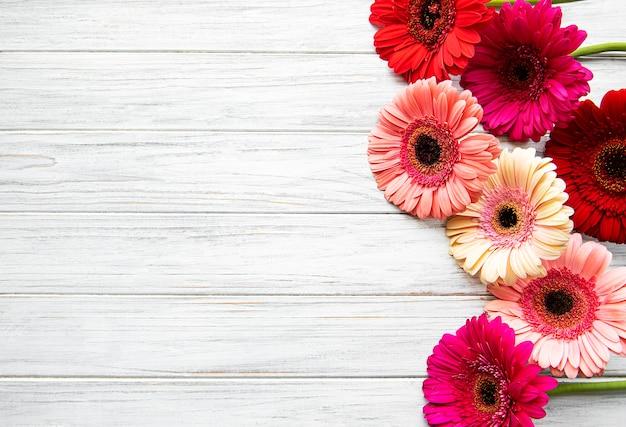 Flores de gerbera brillante sobre un fondo blanco de madera