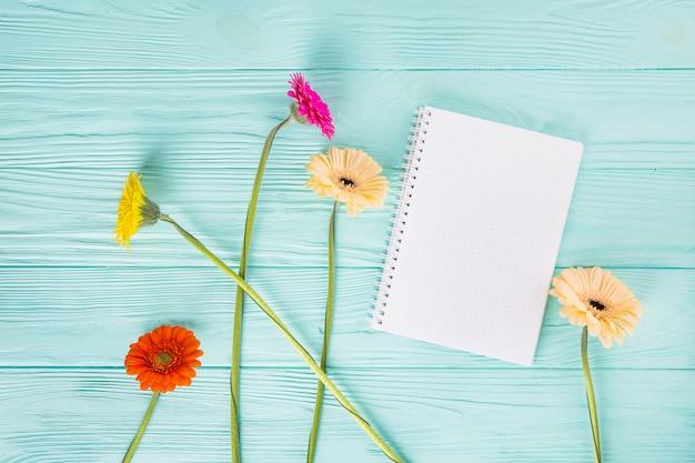 Flores de gerbera con cuaderno en blanco en mesa