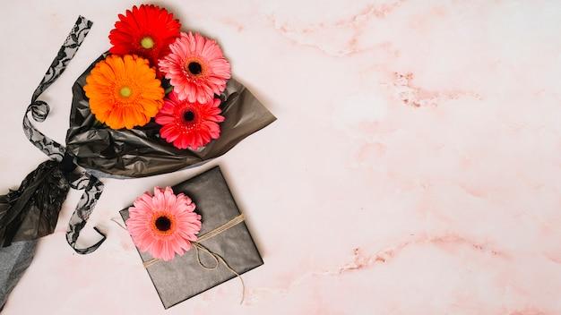 Flores de gerbera en film de embalaje con caja de regalo.