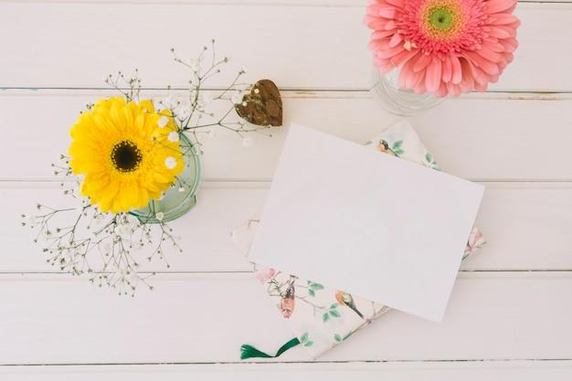 Flores de gerbera en jarrones con papel blanco.