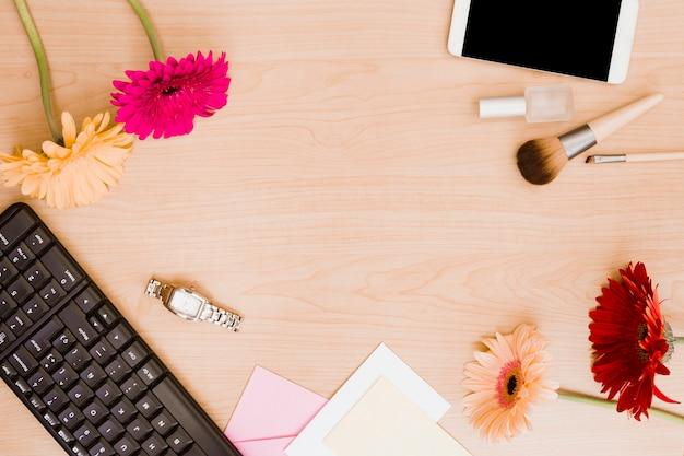 Flores de gerbera; teclado; reloj de pulsera; sobre; brocha de maquillaje; botella de esmalte de uñas y teléfono móvil en el escritorio de madera