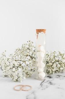 Flores de gypsophila; anillos de boda y malvavisco en tubo de ensayo sobre fondo blanco