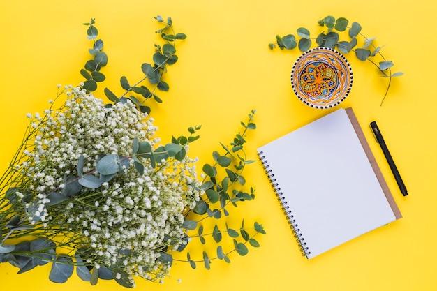 Flores de gypsophila con hojas; bloc de notas espiral cuenco; pluma sobre fondo amarillo