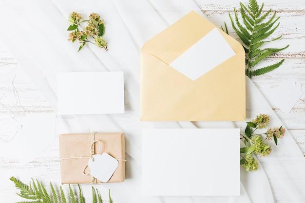Flores; helecho; caja de regalo envuelta; tarjeta; sobre y bufanda en mesa de madera.