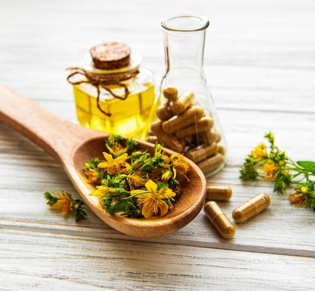 Flores de hierba de san juan con una botella de aceite natural