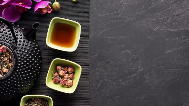 Flores y hojas secas con té de hierbas en mantel negro sobre fondo de textura