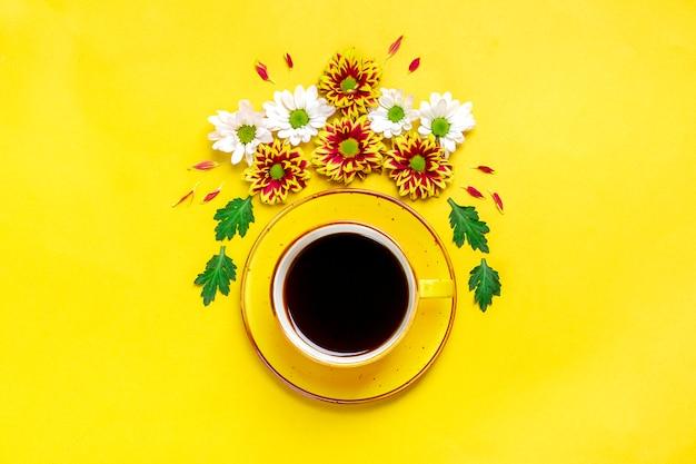 Flores, hojas verdes y una taza de café caliente.