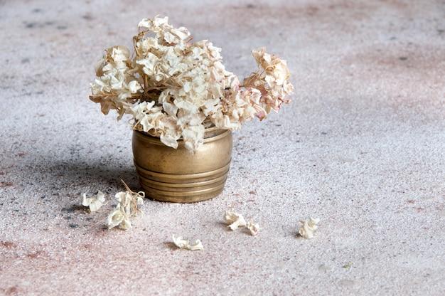 Flores de hortensias secas en un jarrón de latón