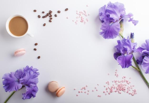 Flores de iris morado y una taza de café en blanco