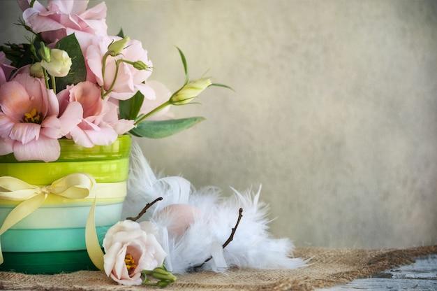 Flores en un jarrón con cinta amarilla y huevo sobre plumas
