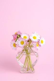 Flores en un jarrón con forma de corazón.