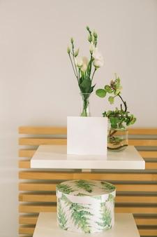 Flores en jarrón con hoja de papel en blanco.