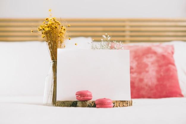 Flores en jarrón con macarrones y papel en blanco.
