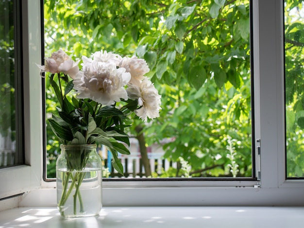 Flores en un jarrón sobre el alféizar de una ventana.