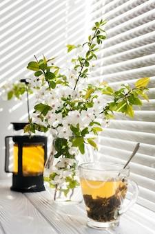 Flores en un jarrón con una taza de té