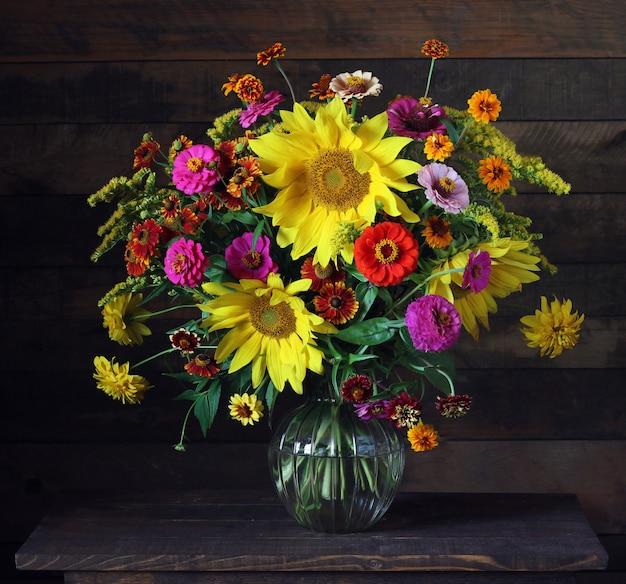 Flores en un jarrón de vidrio sobre la mesa. bodegón con un ramo de flores de jardín.