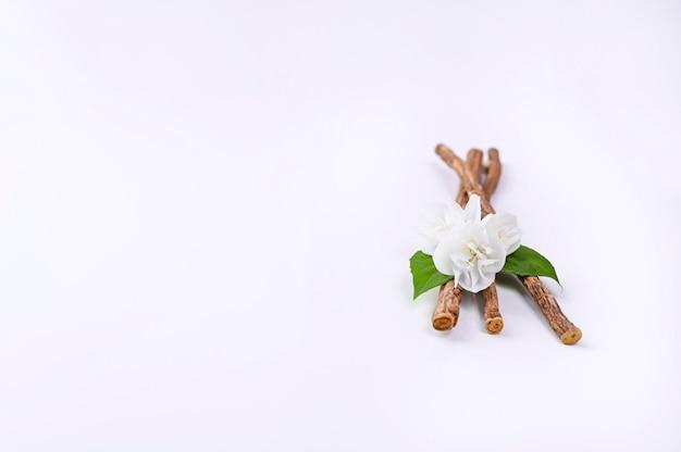 Flores de jazmín y especias sobre un fondo blanco.