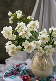 Flores de jazmín en un jarrón blanco. stillife con flores de primavera.