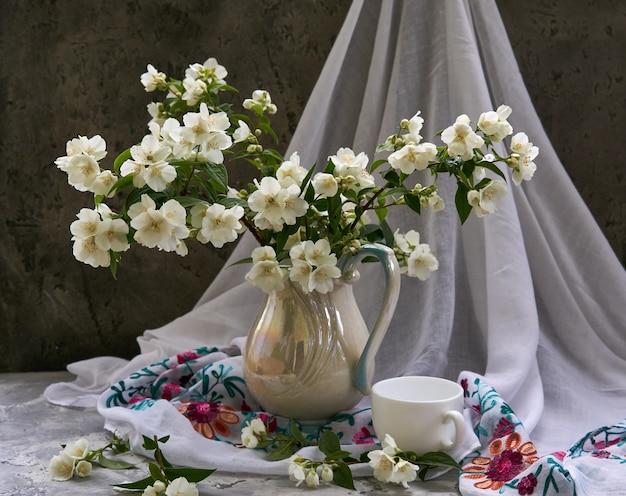 Flores de jazmín en un jarrón blanco. stillife con jazmín y taza de café.
