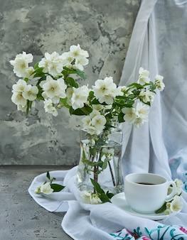 Flores de jazmín en un jarrón de cristal.