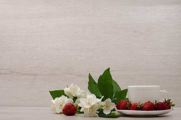 Flores de jazmín, taza blanca, fresas, lugar para texto