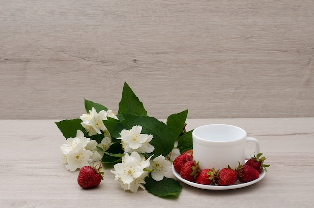 Flores de jazmín, taza vacía blanca, fresas, lugar para texto
