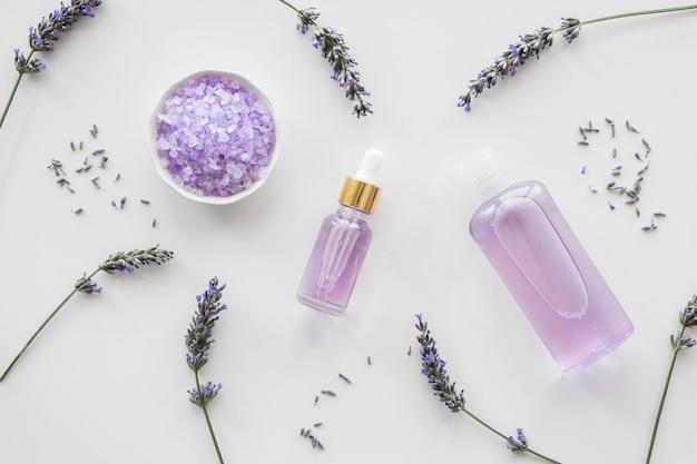 Flores de lavanda y botella de pétalos con perfume.