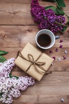 Flores lilas con caja de regalo y taza de café en la mesa de madera.