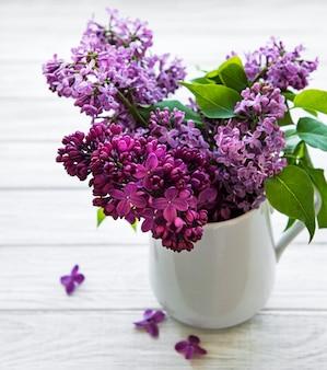 Flores lilas en un jarrón sobre una mesa de madera blanca