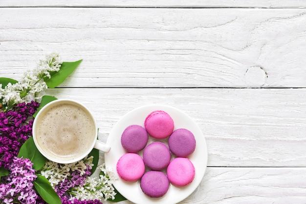 Flores lilas, macarons y taza de capuchino en mesa de madera blanca
