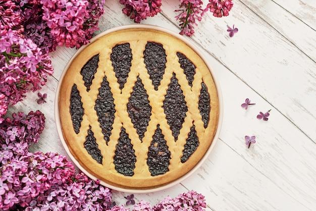 Flores lilas púrpuras con una tarta de arándanos