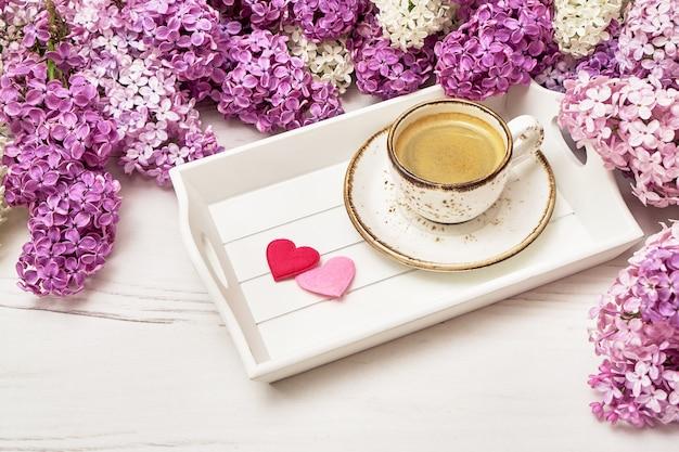 Flores lilas y taza de café con corazones.