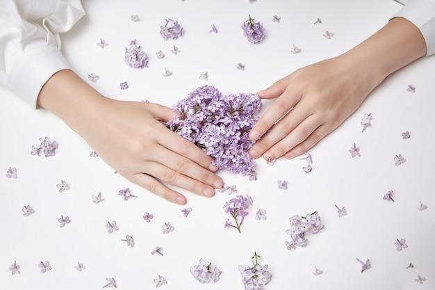 Flores de lirio de primavera en manos de una mujer acostada sobre una mesa blanca. cosmética natural para manos, manos antiarrugas. belleza natural de una mujer