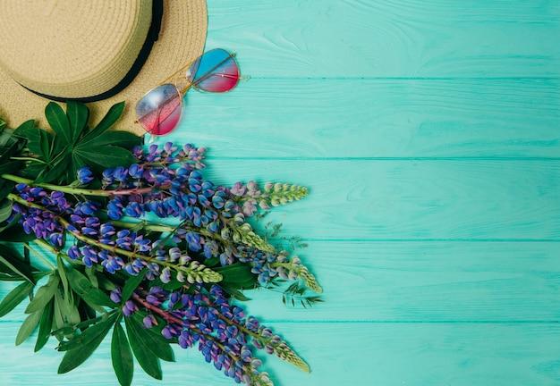 Flores de lupino y accesorios de verano en un fondo de madera