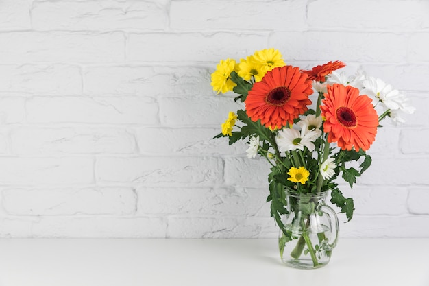 Flores de manzanilla y gerbera en la jarra de vidrio en el escritorio contra la pared de ladrillo blanco