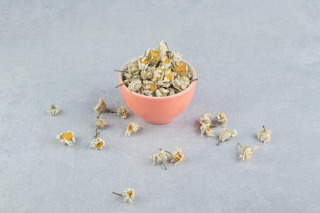 Flores de manzanilla secas en un tazón de naranja.