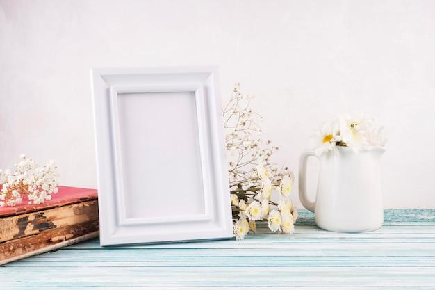 Flores con marco en blanco en mesa de madera