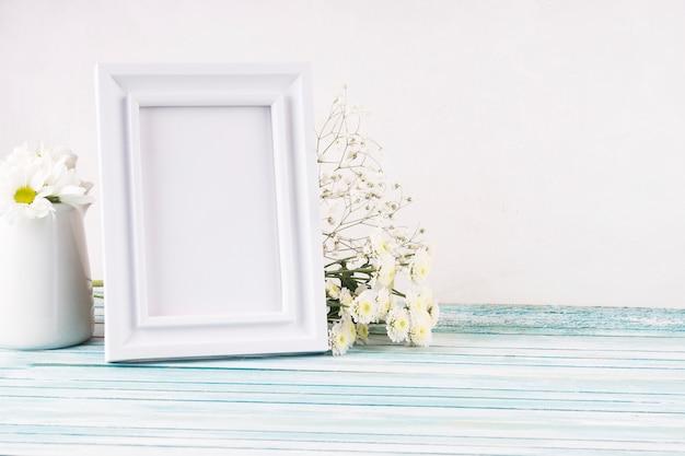 Flores con marco en blanco en mesa