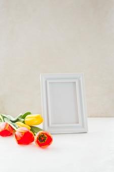 Flores y marco de fotos vacío colocados cerca de la pared