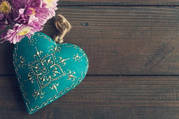 Flores de margarita y corazón decorativo verde azulado
