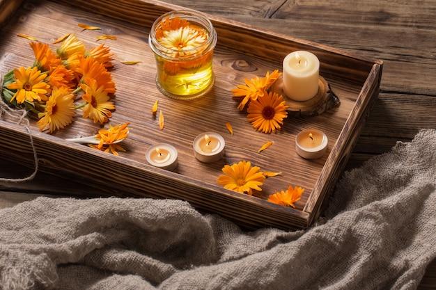 Flores medicinales de caléndula y aceite aromático con velas encendidas en bandeja de madera oscura.