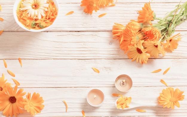 Flores medicinales de caléndula sobre fondo blanco de madera
