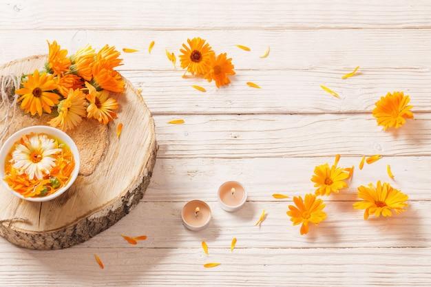 Flores medicinales de caléndula con velas encendidas en madera blanca