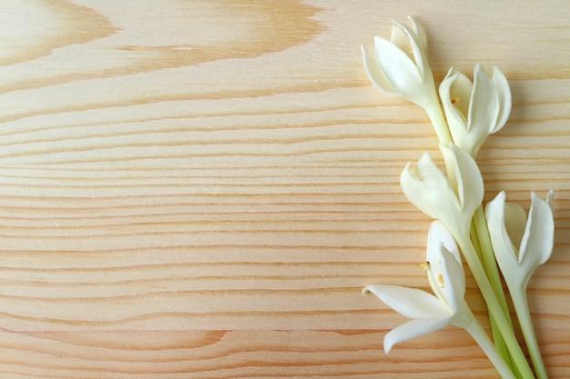 Flores de millingtonia en mesa de madera