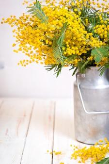 Flores de mimosa en una lata de leche de metal vintage.